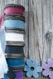Carretéis de madeira coloridos com as fitas de linho no fundo de madeira Foto de Stock