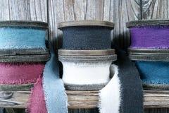 Carretéis de madeira coloridos com as fitas de linho no fundo de madeira Fotografia de Stock Royalty Free