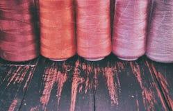 Carretéis retros da linha da foto na costura e no bordado vermelhos da escala Fotografia de Stock