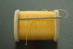 Carrete con el hilo y la aguja amarillos Imagen de archivo