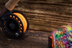 Carrete con la línea anaranjada y cebo de giro en fondo de madera imágenes de archivo libres de regalías