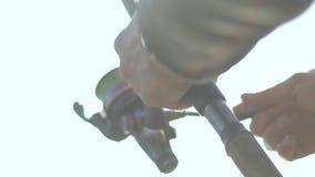 Carrete de giro de la pesca del pescador Fisher da vuelta a la bobina en un pescado de giro del saque cercana para arriba almacen de video