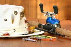 Carrete de la pesca con el sombrero y señuelos del color Fotos de archivo libres de regalías