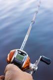 Carrete de la pesca del multiplicador del uso del pescador Fotografía de archivo libre de regalías