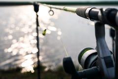 Carrete de la pesca en el borde del lago con el foco en el alambre Imagenes de archivo