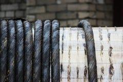 Carrete de madera grande con el cable industrial eléctrico negro Fotos de archivo libres de regalías