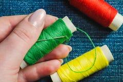Carrete del hilo de coser verde y una aguja en una mano femenina contra la perspectiva de otros carretes del hilo en el dril de a foto de archivo libre de regalías