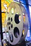 Carrete del proyector del cine Vieja y antigua pieza del proyector de película comercial en un fondo del vitral fotos de archivo libres de regalías