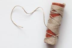 Carrete viejo de la cuerda de rosca en un fondo blanco Fotos de archivo libres de regalías
