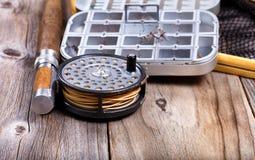 Carrete y engranaje de la pesca con mosca del vintage en fondo de madera rústico fotos de archivo libres de regalías