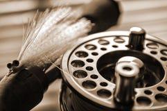 Carrete y señuelo de la pesca de mosca en muelle Fotos de archivo