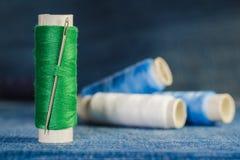 Carretel da linha verde com uma agulha no fundo dos carretéis da linha azul e branca em uma sarja de Nimes fotografia de stock