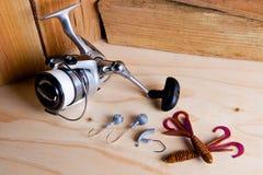 Carretel da pesca com iscas do silicone no fundo de madeira Fotografia de Stock Royalty Free