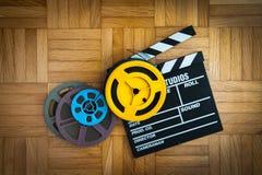 Carretel de placa e de filme de válvula do filme no assoalho de madeira Foto de Stock