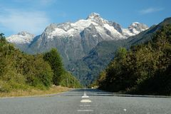 Carretera Austral road trip, jagged mountain over road. Road on the Carreteral Austral in Chile.  The straight road between green forest disappears below jagged stock images