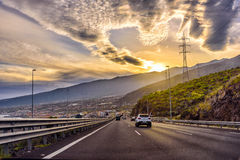 Carretera auto con pequeño tráfico durante puesta del sol en la isla de Tenerife, España Fotografía de archivo libre de regalías