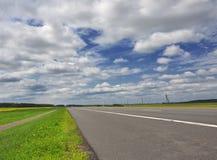 Carretera bajo el cielo nublado azul Fotografía de archivo libre de regalías