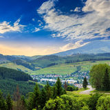 Carretera con curvas al pueblo en montañas Imagen de archivo libre de regalías