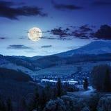 Carretera con curvas al pueblo en montañas en la noche Fotos de archivo