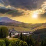 Carretera con curvas al pueblo en montañas en la puesta del sol Foto de archivo libre de regalías