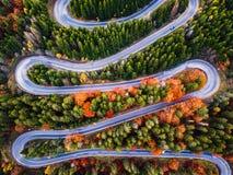 Carretera con curvas del paso de alta montaña, en la estación del otoño, con el bosque anaranjado imagenes de archivo