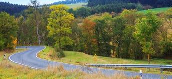 Carretera con curvas en el bosque otoñal Fondo de la naturaleza fotos de archivo