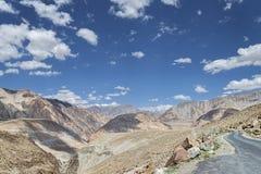 Carretera con curvas remota entre las montañas capsuladas alta nieve imagen de archivo libre de regalías