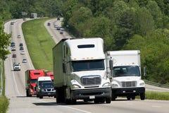 Carretera con los camiones y otros vehículos Imagenes de archivo