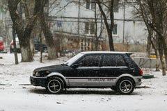 Carretera con los coches parqueados durante nevadas imagenes de archivo