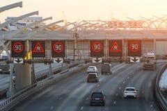 Carretera de alta velocidad con los coches del tráfico y muestras del límite de velocidad y una advertencia resbaladiza del camin Fotos de archivo libres de regalías