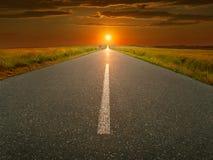Carretera de asfalto abierta, recta en la puesta del sol fotografía de archivo