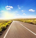 Carretera de asfalto al sol Foto de archivo libre de regalías