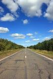 Carretera de asfalto bajo el cielo azul Fotografía de archivo libre de regalías