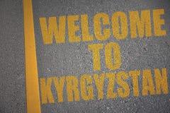 carretera de asfalto con la recepción del texto a Kirguistán cerca de la línea amarilla Fotos de archivo libres de regalías