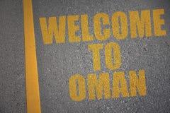 carretera de asfalto con la recepción del texto a Omán cerca de la línea amarilla Foto de archivo libre de regalías