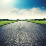 Carretera de asfalto debajo de los cielos azules anchos Foto de archivo