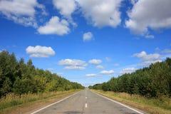 Carretera de asfalto debajo del cielo azul Fotos de archivo libres de regalías