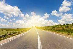 Carretera de asfalto del verano en salida del sol al sol Campo amarillo hermoso fotos de archivo