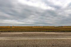 Carretera de asfalto delante de un campo con una pared larga de las pilas del heno foto de archivo libre de regalías