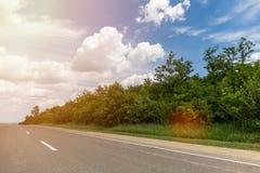 Carretera de asfalto, el cielo con las nubes y árboles fulgor imagenes de archivo