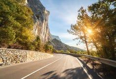 Carretera de asfalto en bosque del otoño en la salida del sol Montañas crimeas Fotos de archivo libres de regalías