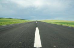 Carretera de asfalto en campo Imagenes de archivo