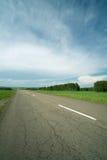 Carretera de asfalto en campo Imagen de archivo libre de regalías