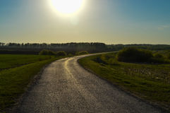 Carretera de asfalto en un campo por la tarde Fotos de archivo libres de regalías