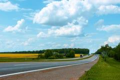 Carretera de asfalto en un paisaje de la primavera Imagen de archivo libre de regalías