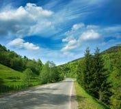 Carretera de asfalto entre las montañas del bosque en el cielo dramático Fotografía de archivo