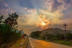 Carretera de asfalto fuera de la ciudad en la puesta del sol Fotografía de archivo libre de regalías