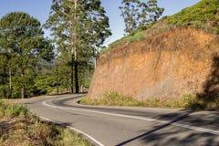 Carretera de asfalto a lo largo de la montaña fotos de archivo