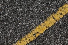 Carretera de asfalto negra con la línea divisoria amarilla Fotos de archivo libres de regalías