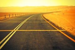 Carretera de asfalto negra de enrrollamiento a través de las dunas de arena del oasis de Liwa, United Arab Emirates Imágenes de archivo libres de regalías